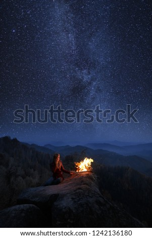 Young blonde woman resting near bonfire outdoor at starry night. Milky Way at mountains. Camp fire on a top of a mountain. Burning fire at dusk on the mountains. Night colorful landscape #1242136180