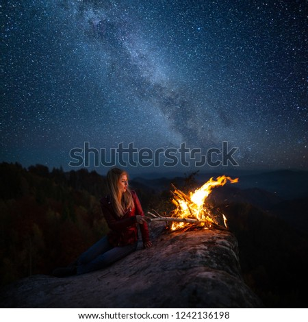Young blonde woman resting near bonfire outdoor at starry night. Milky Way at mountains. Camp fire on a top of a mountain. Burning fire at dusk on the mountains. Night colorful landscape #1242136198