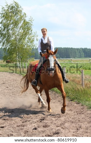 Young blonde woman riding chestnut horse
