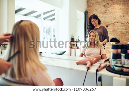 Young blonde woman sitting in a salon chair looking at her reflection in a mirror during an appointment with her hairstylist