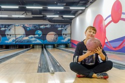 Young blonde woman sitting on floor in bowling club is holding bowling ball on background of empty tracks and pins. Active leisure. Sports family activities. Space for text. Blurred background