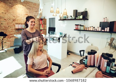 Young blonde woman smiling and looking at her reflection in a mirror while sitting in a salon chair during an appointment with her hairstylist