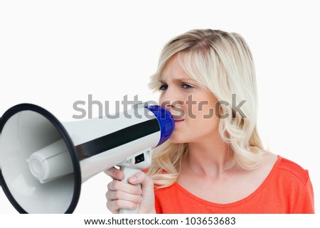 Young blonde woman speaking into a megaphone against a white background