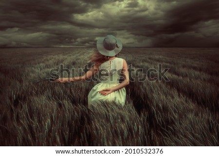 Young blonde woman standing in a wheat field, wearing a yellow summer dress, on a windy and stormy day Foto stock ©