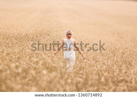 Young blonde woman standing on golden wheat field and touching wheat ears at sunny day. Enjoying nature. Beautiful girl in the rays of sunlight. Sunlight. #1360714892