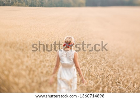 Young blonde woman standing on golden wheat field and touching wheat ears at sunny day. Enjoying nature. Beautiful girl in the rays of sunlight. Sunlight. #1360714898