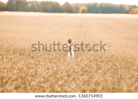 Young blonde woman standing on golden wheat field and touching wheat ears at sunny day. Enjoying nature. Beautiful girl in the rays of sunlight. Sunlight. #1360714901