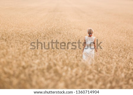 Young blonde woman standing on golden wheat field and touching wheat ears at sunny day. Enjoying nature. Beautiful girl in the rays of sunlight. Sunlight. #1360714904