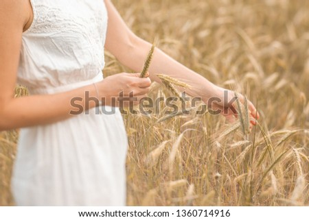 Young blonde woman standing on golden wheat field and touching wheat ears at sunny day. Enjoying nature. Beautiful girl in the rays of sunlight. Sunlight. #1360714916