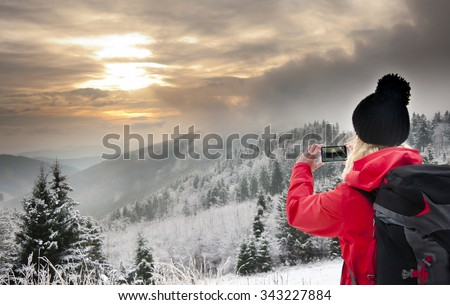 Young blonde woman taking picture of sunset in Jeseniky mountains, Czech Republic