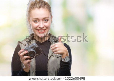 Young blonde woman taking pictures using vintage camera over isolated background happy with big smile doing ok sign, thumb up with fingers, excellent sign