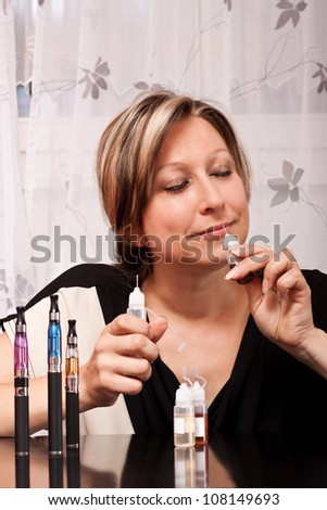 Young blonde woman tests the scent of their liquid flavorings for the e cigarette