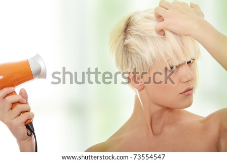 Young blonde woman using hair drier