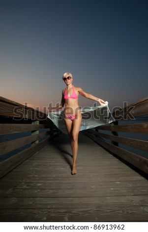 Young Blonde Woman walking on a boardwalk and drying off