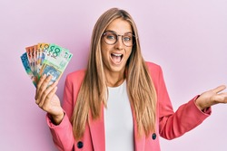 Young blonde woman wearing business style holding australian dollars celebrating achievement with happy smile and winner expression with raised hand