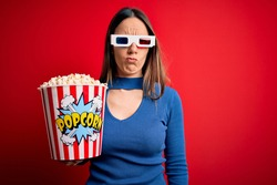 Young blonde woman wearing 3d glasses and eating pack of popcorn watching a movie on cinema depressed and worry for distress, crying angry and afraid. Sad expression.