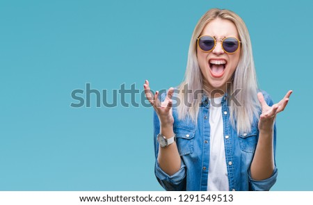 Young blonde woman wearing sunglasses over isolated background celebrating mad and crazy for success with arms raised and closed eyes screaming excited. Winner concept #1291549513
