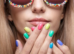 Young blonde woman with fun candy glasses and varicoloured finger nails manicure.
