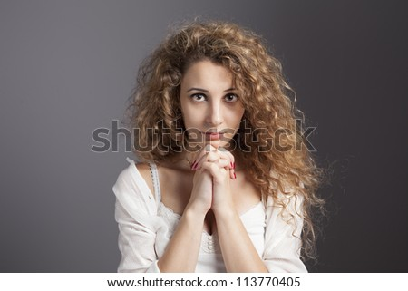 young blonde woman with her hands together praying