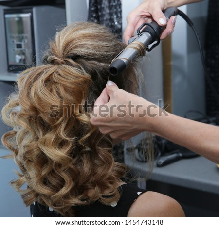 Young blonde woman with long hair in hair salon. Barber makes a hairdress to blonde, curling curls curling iron. Concept for hairdressers and barbershop.