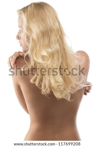 young blonde woman with naked torso and long wavy hair, looks at left and has the right hand on the left shoulder - stock photo