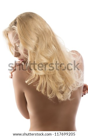 young blonde woman with naked torso and long wavy hair, she looks down at left and has the right hand on the left shoulder