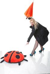 young blonde woman with umbrella kicks big plaything