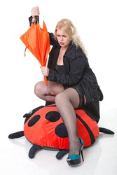 young blonde woman with umbrella straddles big plaything
