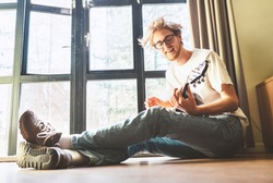 Young blondhair handsom man plays on guitar sitting on floor near the whole wall window at home. Funny freetime spending concept image.