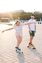 young blondhaired woman longboarding with her partner, boths are in the bright shorts of pink