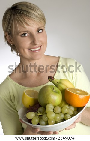 young blondie holding bowl with fresh fruits