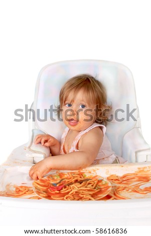 Young blue eyed baby girl making a mess with spaghetti in tomato sauce on a white background