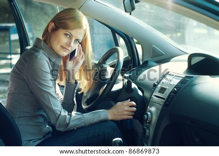 Young blue-eyed businesswoman talking on the cell phone inside her car