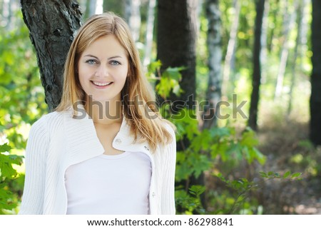young blue-eyed smiling woman in white against blurred forest background with selective focus and copy space