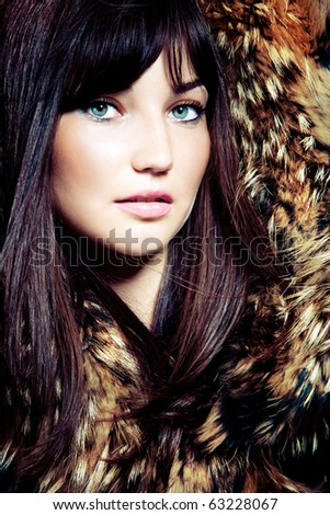 young blue eyes woman portrait with fur, studio shot