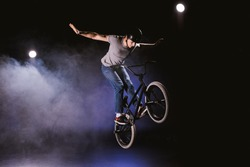 young bmx cyclist in helmet performing stunt and jumping with bicycle in smoke