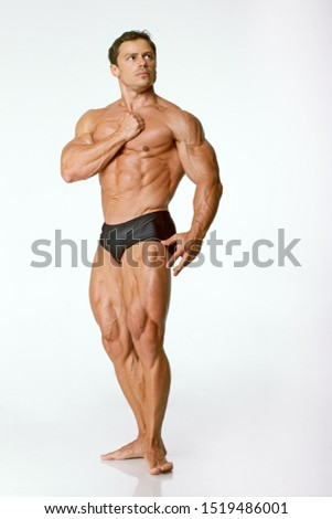 Young bodybuilder athlete demonstrates muscles on a white background. The muscles of the arms, chest and legs are visible. The right arm is tense and pressed to the chest.