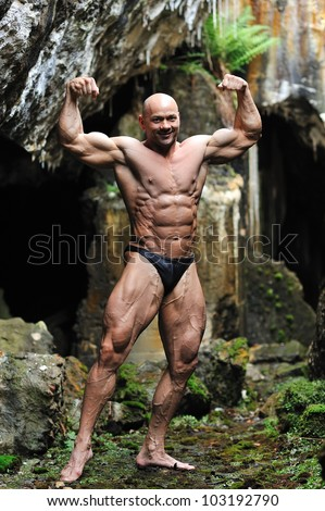 Young bodybuilder posing in a cave - Front view