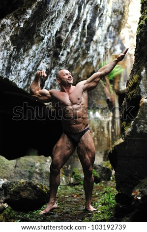 Young bodybuilder posing in a cave - front view in full length portrait