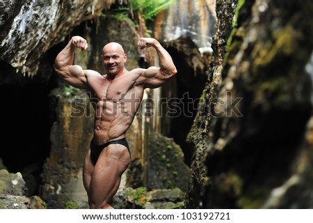 Young bodybuilder posing in a cave - Perfect body