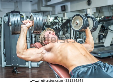 Young bodybuilder training hard. Pectoral work out with weights