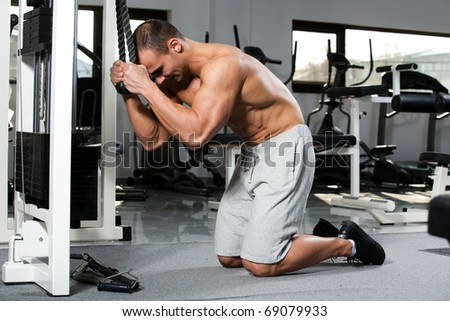 young bodybuilder training in the gym: Abdomens - Cable Crunch, start position