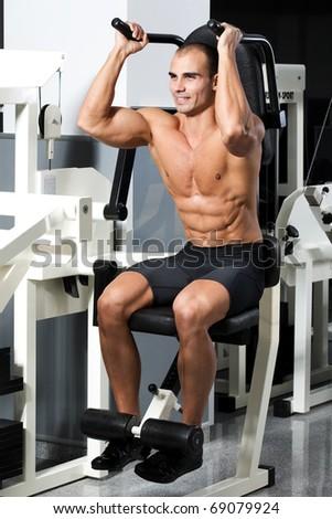 young bodybuilder training in the gym: Abdominals - Crunch Machine, start position - stock photo