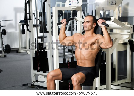 young bodybuilder training in the gym - machine shoulder press, start position