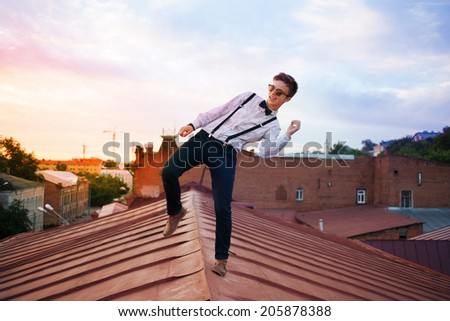 Young bold girl woman hipster jumping on the roof, dressed like a boy man in a shirt, bow-tie, suspenders and pants trousers