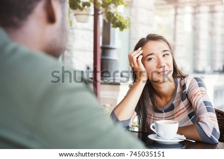 Young bored girl sitting and drinking coffee on date with her boyfriend at cafe. Speed dating, unsuccessful meeting