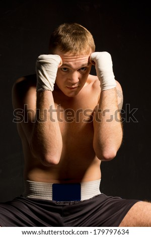 Young boxer protecting his head by raising both his bandaged fists in a defensive position against a dark background