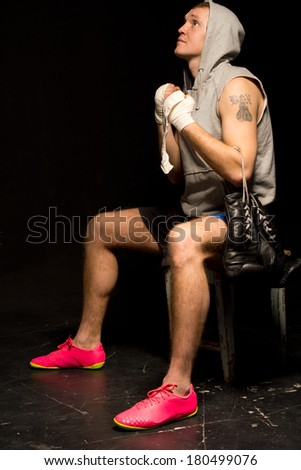 Young boxer psyching himself up before a match sitting on a stool with clasped hands looking up to the heavens for help in securing a victory