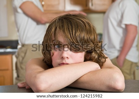 Young boy, age 12, crying (or about to cry) during family argument - stock photo