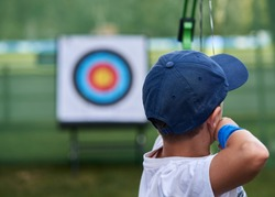 Young Boy aims a target with his bows and arrows